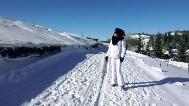 woman walking on snow mountain road
