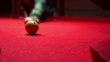 Close up of man playing billiards on red background