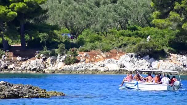 Kleines Boot mit Touristen auf der Meeresoberfläche mit Insel im Hintergrund