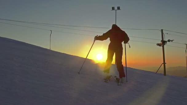 Woman on skis climbs mountain on sunset background