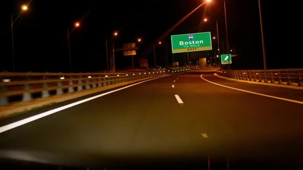 Driving on Highway at night with exit sign of Boston city, Massachusetts