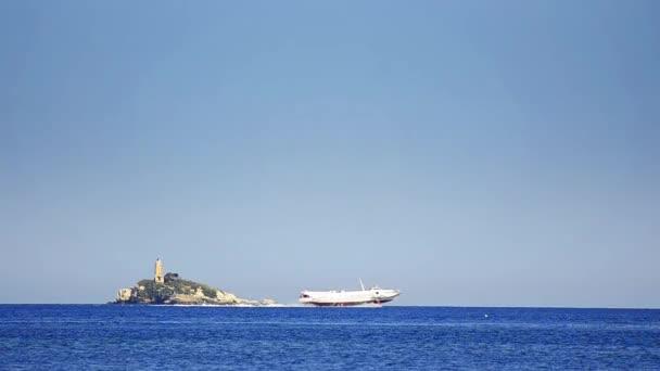 Schnelle Speedboot fliegen auf der Meeresoberfläche Wellen mit Leuchtturm Insel im Hintergrund. hd 1080p.