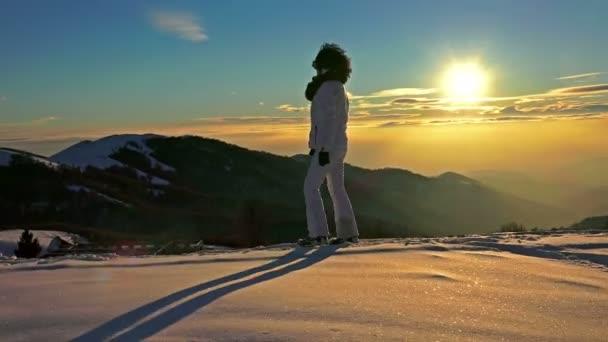 woman enjoying during winter snow walking on sunset background