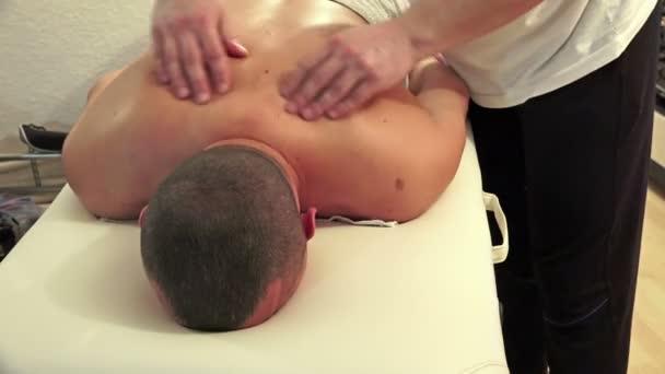 Adult man gets body massage at spa salon