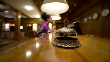Female visitor on hotel reception pushing on bell