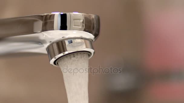 Open chrome faucet washbasin water flow loop background cinematic dof