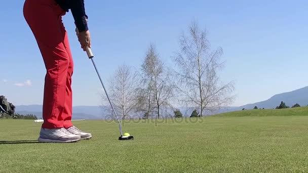 Nízký úhel ženské golfové hráče v zasažení míčku zpomaleně