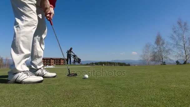 Low angle of male golf player practising in hitting of ball