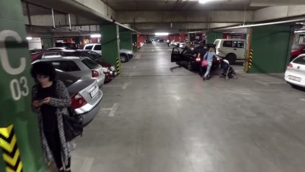 POV at large busy underground parking of shopping mall