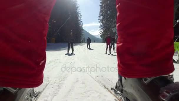 Nahaufnahme von Männerbeinen und Skischuhen. er rutscht langsam den Abhang hinunter.