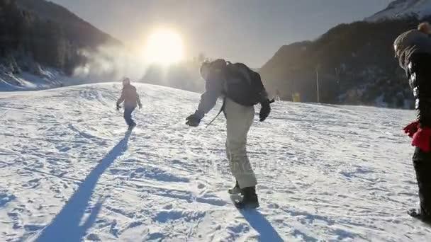 Three young girls walk through the snow ski slope backlit by sunset sun. Trekking shot