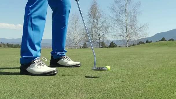 Nízký úhel mužské golfové hráče v zasažení míčku zpomaleně