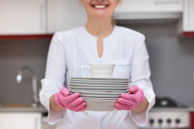Smiling woman holding porcelain plates