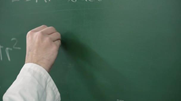 Kézfogás kréta és írás egy matematikai képlet vagy egyenlet a táblán.
