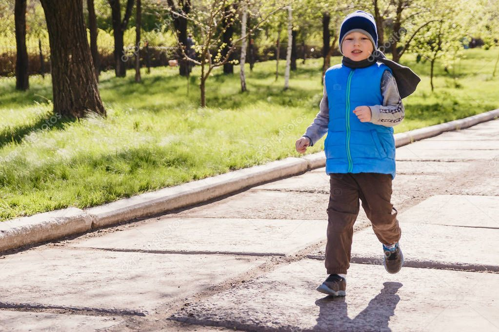 the boy five years old in a blue vest running through the spring