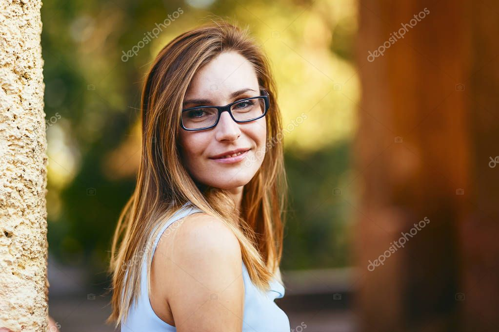 cheerful happy attractive young woman thirty years old with glasses on the street in summer