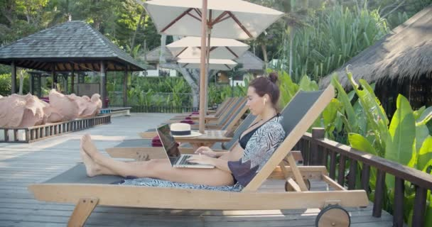 mladá modelka relaxuje na dřevěné palubě mimo tropické lázně, pracuje na svém notebooku