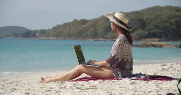 Csinos nő dolgozik a laptop a parton, körülnéz, élvezi az idejét