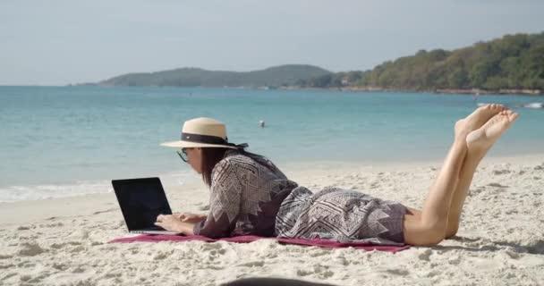 fiatal modell fehér szalma kalap és pihenőköpeny feküdt törölköző a homokos tengerparton