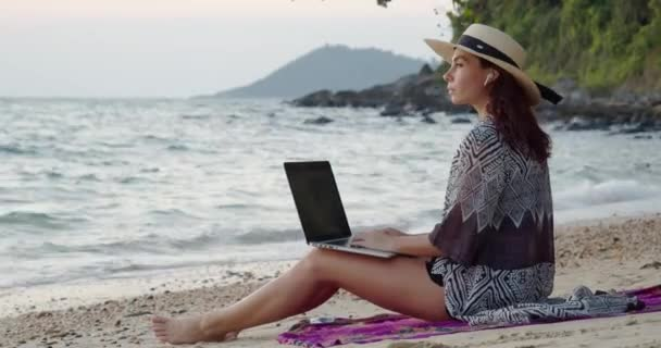 fiatal csinos turista szalma kalap egy laptop a térdén ül a homokos tengerparton