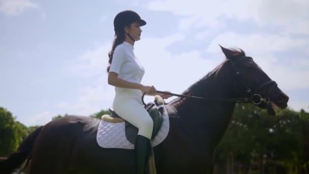hübsches Mädchen mit Helm und Stiefeln auf braunem Pferd, das auf der Reithalle schreitet, Ausritt an der frischen Luft Reiterfreizeitaktivitäten