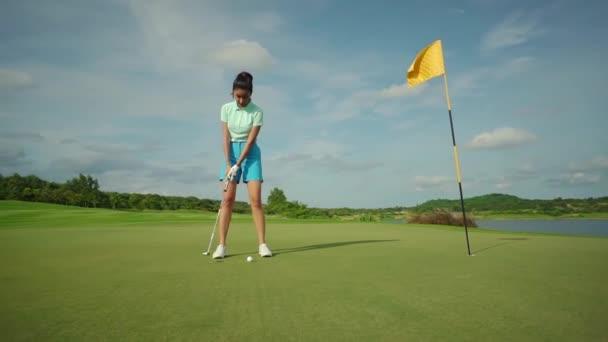krásná dívka v modrých kraťasech hraje golf trénink backswing na zelené hřiště skvělý čas na dovolenou v horkých zemích