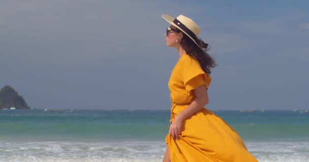 mladá žena ve žlutých šatech a slamák chůze podél písečné pláže v odpoledních hodinách s odpočinkem skvělá nálada pod tropickým sluncem