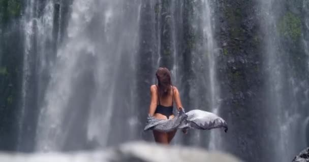 back view of breathtaking young model posing at mountain waterfall, amazing scenery of tropical jungle wildlife