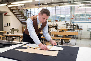 Tailor working with paper patterns on new jacket