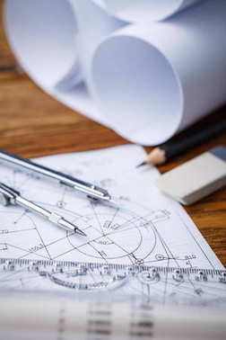 Architectural blueprints and blueprint rolls and a drawing instruments on the worktable.