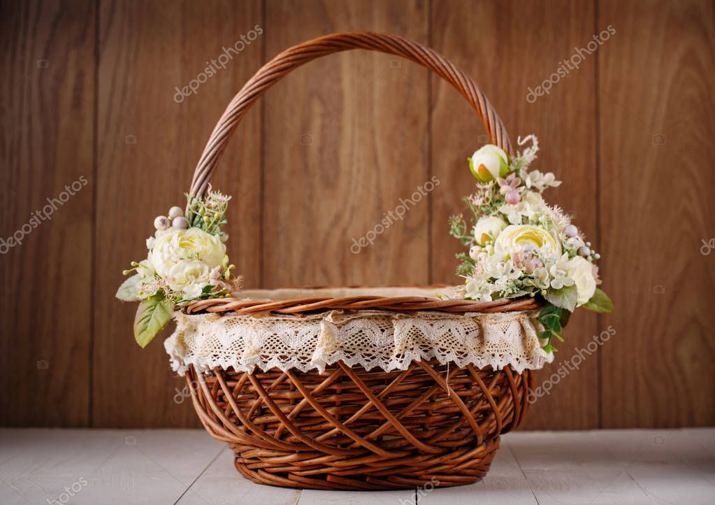 Designer basket is decorated with flowers. Wicker basket for celebrating Easter and other holidays.