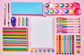 Photo Bright composition from a school stationery on a pink background