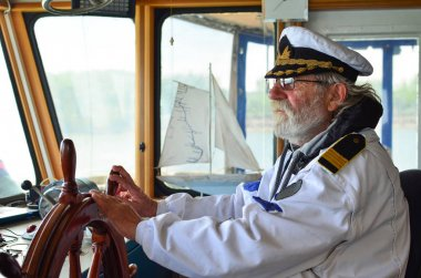 Old experienced captain in navigation cabine