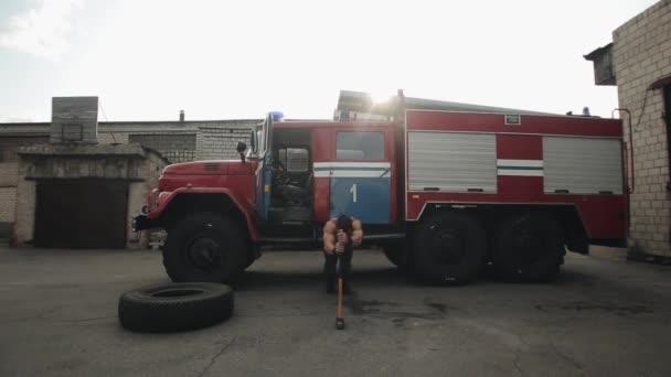Svalnatý pohledný sportovec dělá kliky s kladivem před hasičským strojem