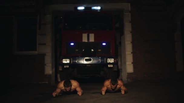 Dva svalnatí sportovci bez trička dělají extrémní kliky před hasičským vozem s blikajícími nouzovými světly a sirénami v noci venku