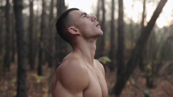 Mladý atletický chlap s nahým trupem stojí v lese a dělá dechové cvičení. podzimní listí padá ze stromů. Zpomalený pohyb.