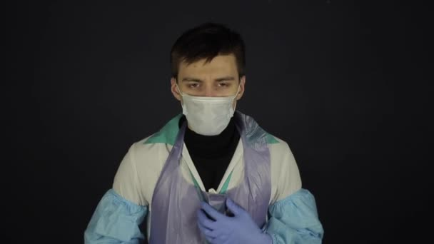 A young caucasian man coughing and putting on a medical mask. Isolated black background. Coronavirus COVID19