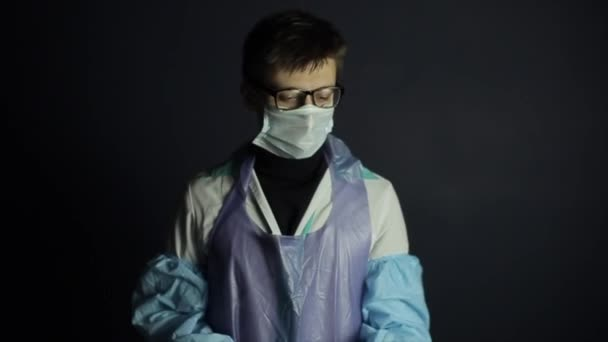 A scientist in protective clothing looking at a coronavirus COVID-19 model. Dark background.