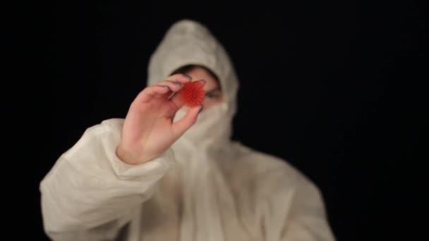 Egy fehér doktornő védőruhában, aki a COVID-19-es modellekre mutat. Sötét háttér. Elszigetelve. Kezeket fel! Női tudós