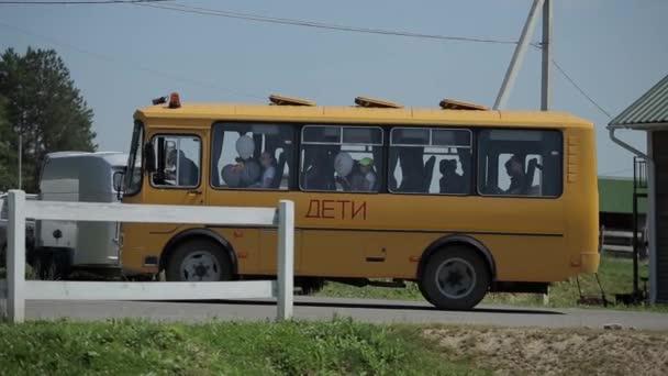 Minszk, Fehéroroszország - 2019. július 19.: Közelkép egy kis sárga buszról, amelyen léggömböket tartó gyerekek hagyják el a vidéket. Oldalnézet