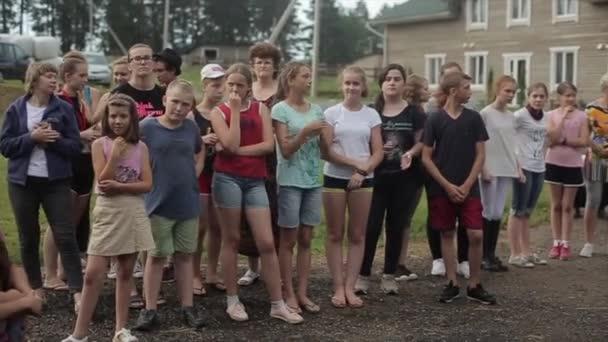 Minsk, Weißrussland - 19. Juli 2019: Erwachsene und Jugendliche stehen an einem Sommertag in einer Gruppe vor der Kulisse von Natur und Häusern und applaudieren