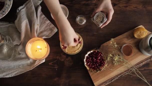 Egy fiatal lány hagyományos humuszt főzött a konyhájában, és fűszerekkel locsolta. Közelkép. Kilátás felülről