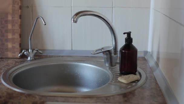 Egy fiatal európai lány csíkos szappannal mossa a kezét a csap alatt. Koronavírus. COVID-19 szám