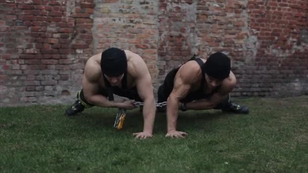 A férfiak tornáznak és edzenek. Két fiatal izmos férfi a szinkron fekvőtámasznál az egyik kezével a földről. A kamera fel-le mozog..