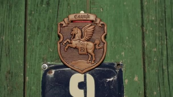 Bobruisk, Belarus - 20 April 2020: Wooden door of a village house with the coat of arms of one of the Slavic cities with a horse. Close-up. Slutsk