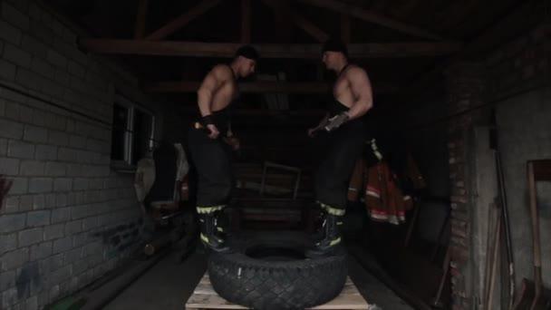 Dva svalnatí mladí muži trénují a dělají křížová cvičení tím, že vyskočí na pneumatiku s kladivy v rukou. Kamera se pohybuje nahoru a dolů