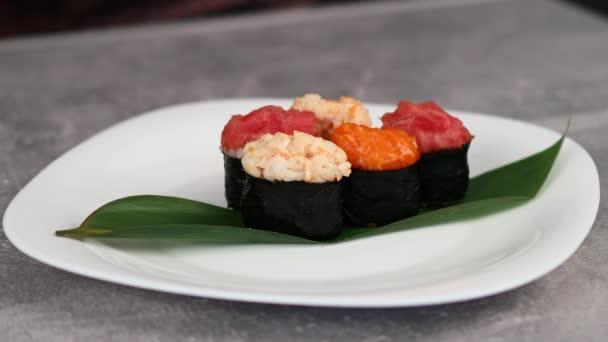 Japán sushi ovális gunkan-maki különböző típusú feltétekkel, nori levelekbe csomagolva egy nagy tányéron. Makrofelvétel