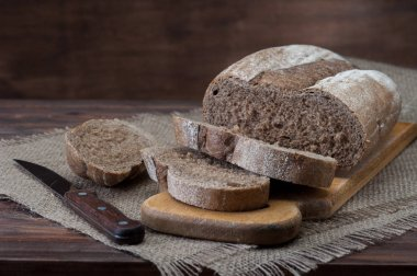 Dark sliced bread with knife on the wooden table.