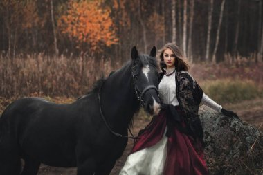 Beautiful young woman with a horse outdoor. Brunette young girl