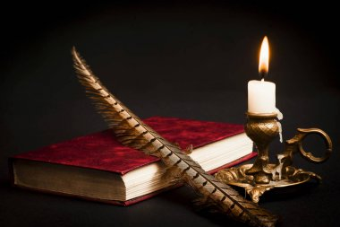 Bir kalem bir kitap ve bir mum yanan bir mum